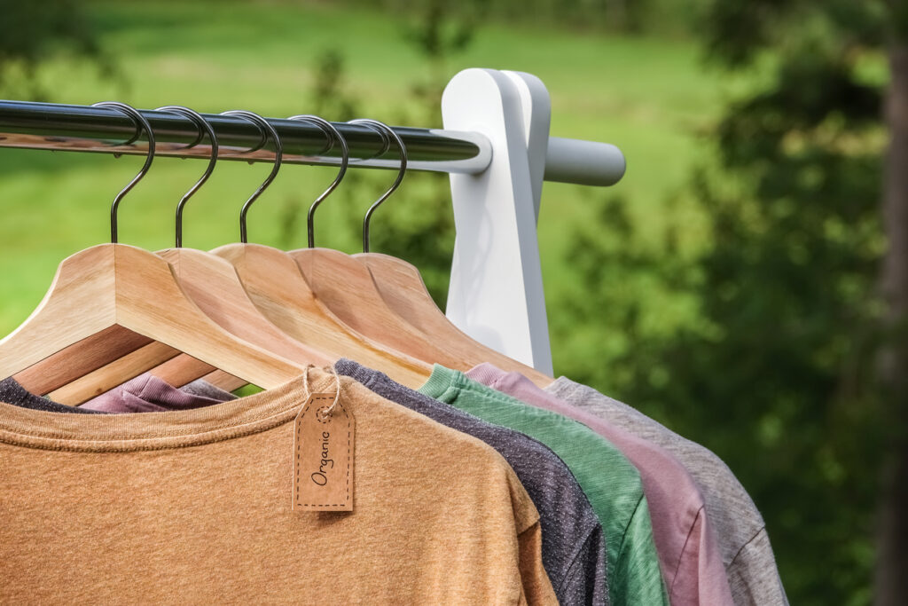 Organic clothes, t shirts hanging on wooden hangers with green forest, nature in background.